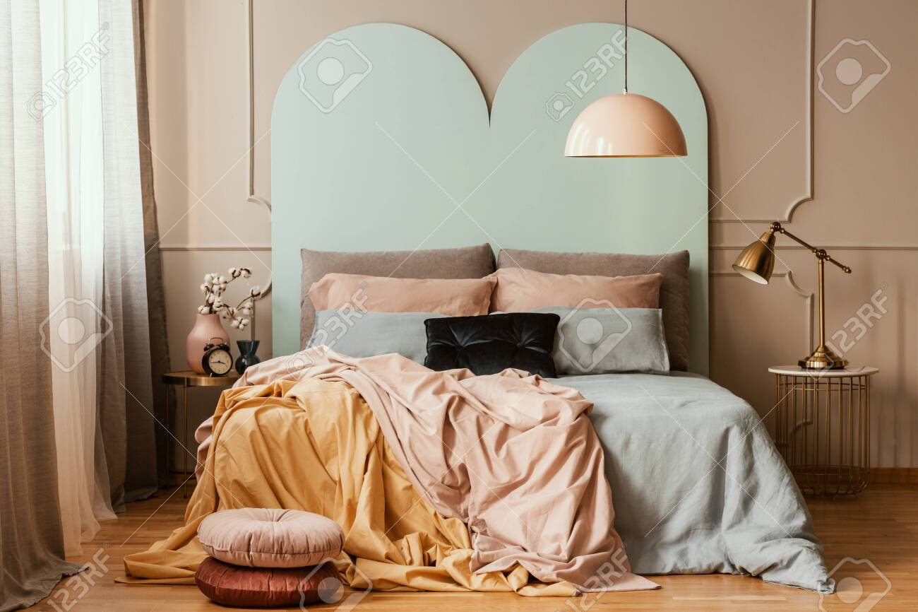 Pastel blue, pink and orange bedding on double bed in chic bedroom..