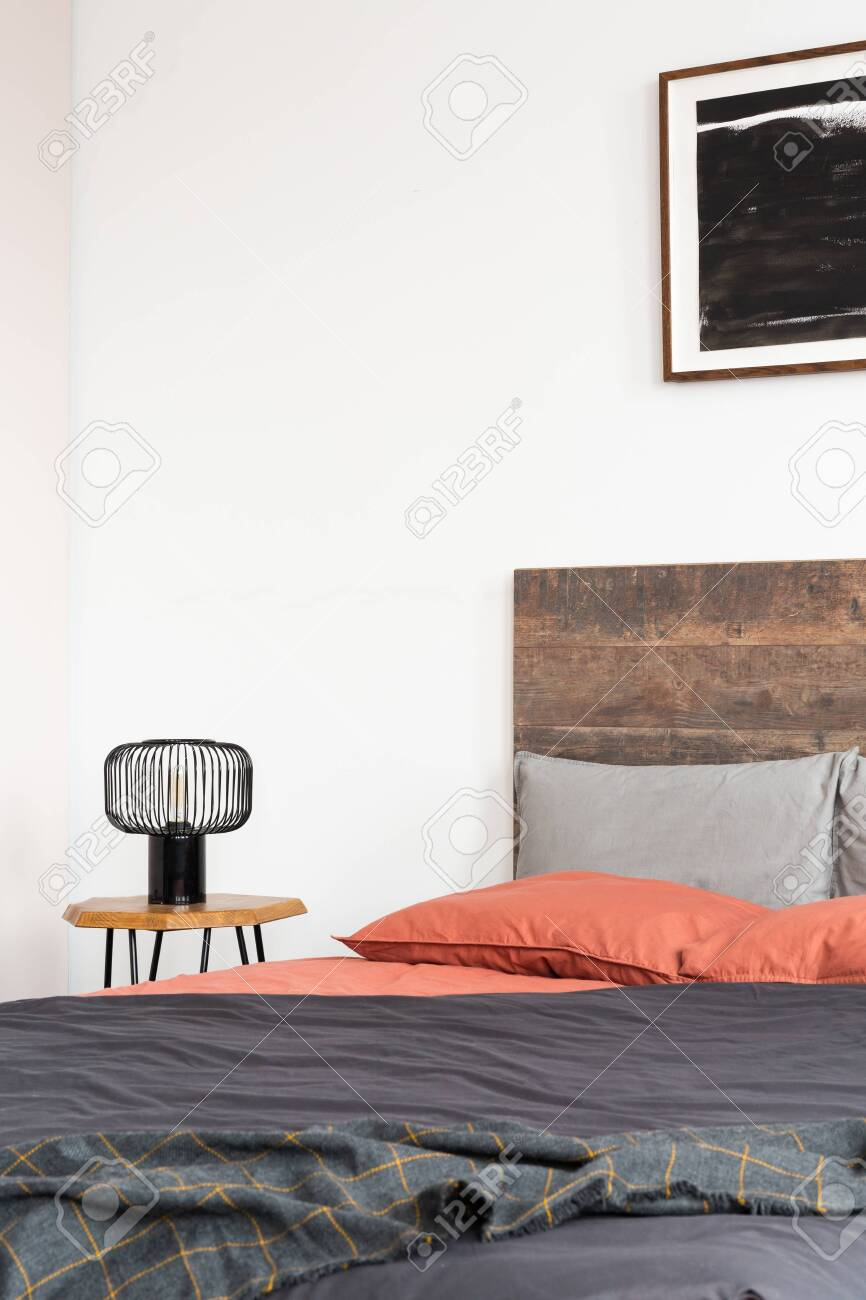 Closeup Of Lamp On Wooden Nightstand And Black Poster On The Stock Photo Picture And Royalty Free Image Image 129348303