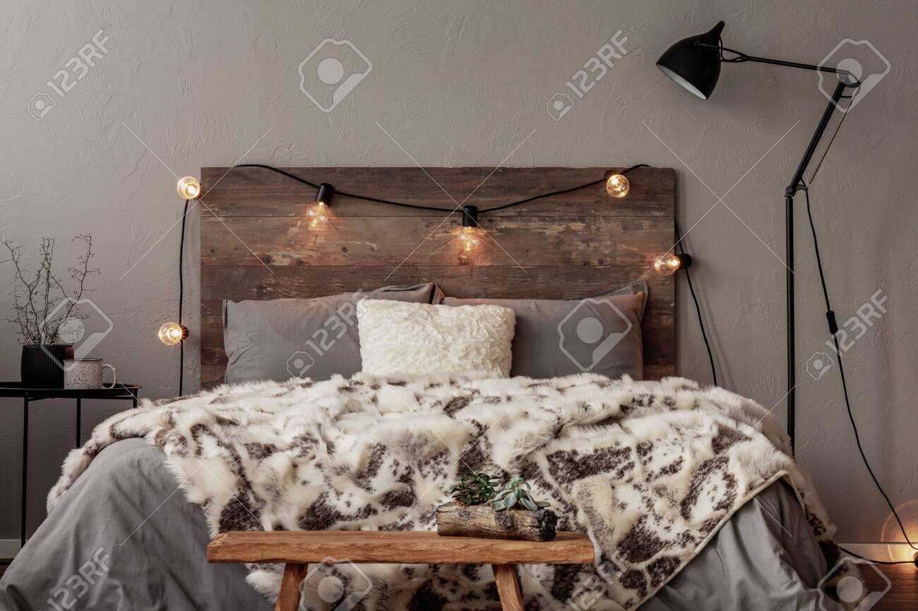Light bulbs on wooden headboard of comfortable bed with grey..