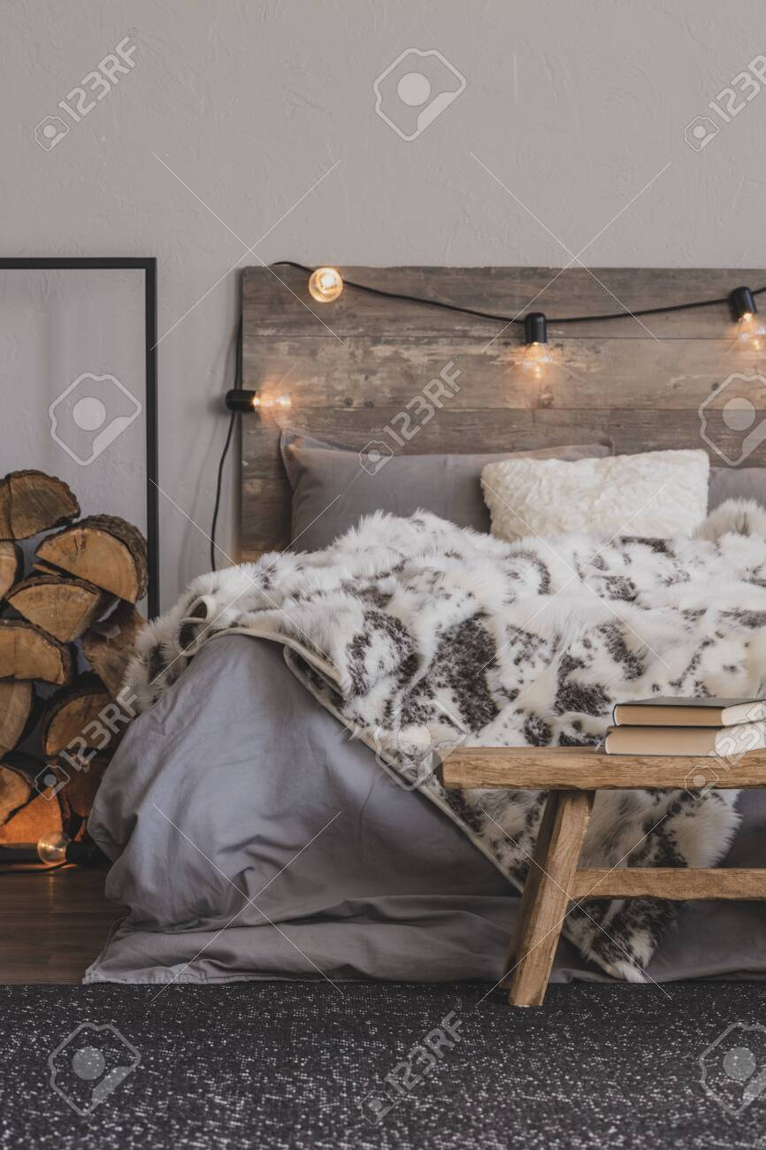 Wooden bench with book in foot of the bed of cozy bedroom interior..