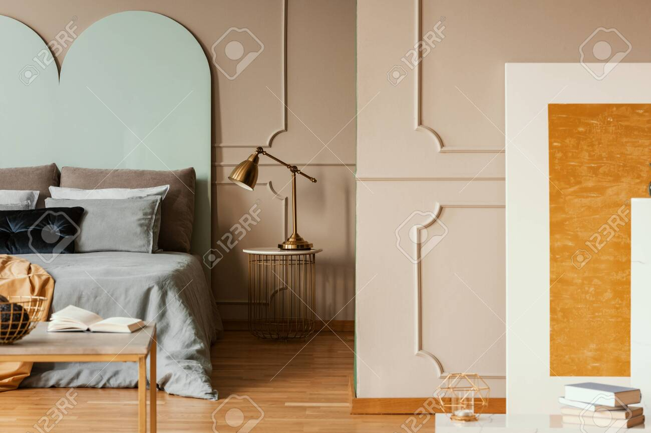 Golden lamp on modern nightstand table next to blue bed in grey bedroom interior - 138291935