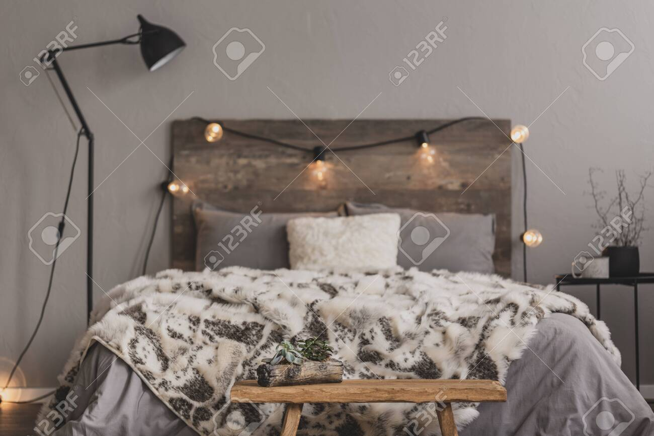 Foot Of The Bed wooden bench in the foot of the bed with grey bedding and cozy..
