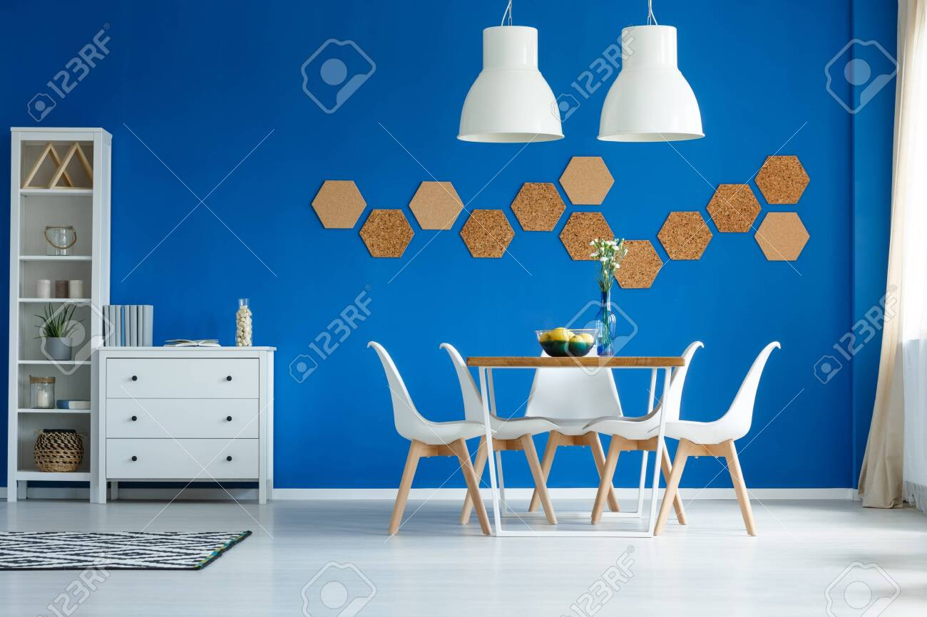 Cork honeycombs on blue wall of white living room with dining area - 140515582