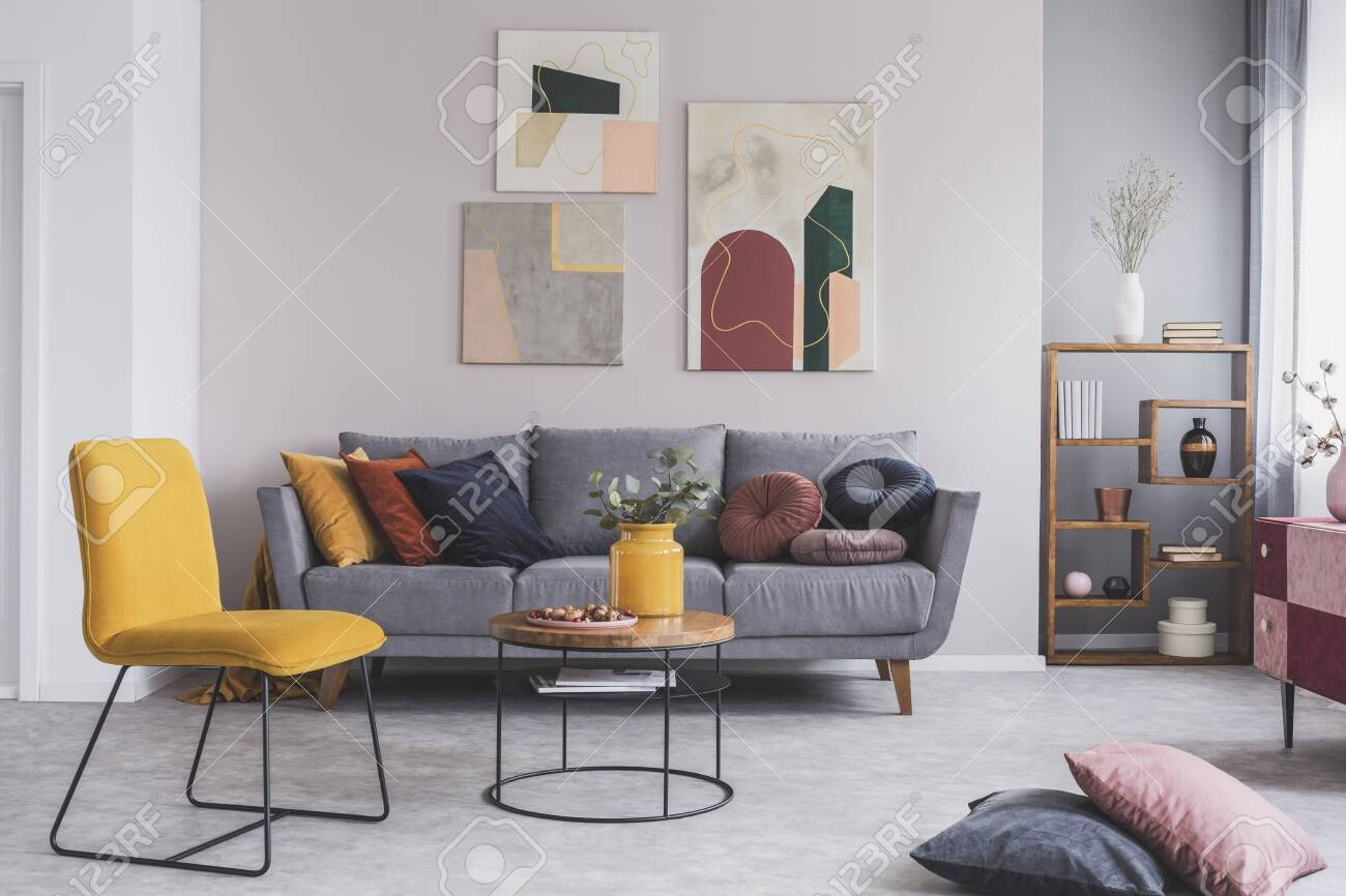 Real photo of a yellow chair and gray couch with pillows in a modern living room interior - 140518325