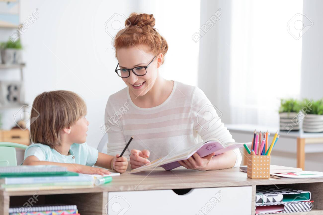 Happy mother and smiling son doing homework at desk - 145313769