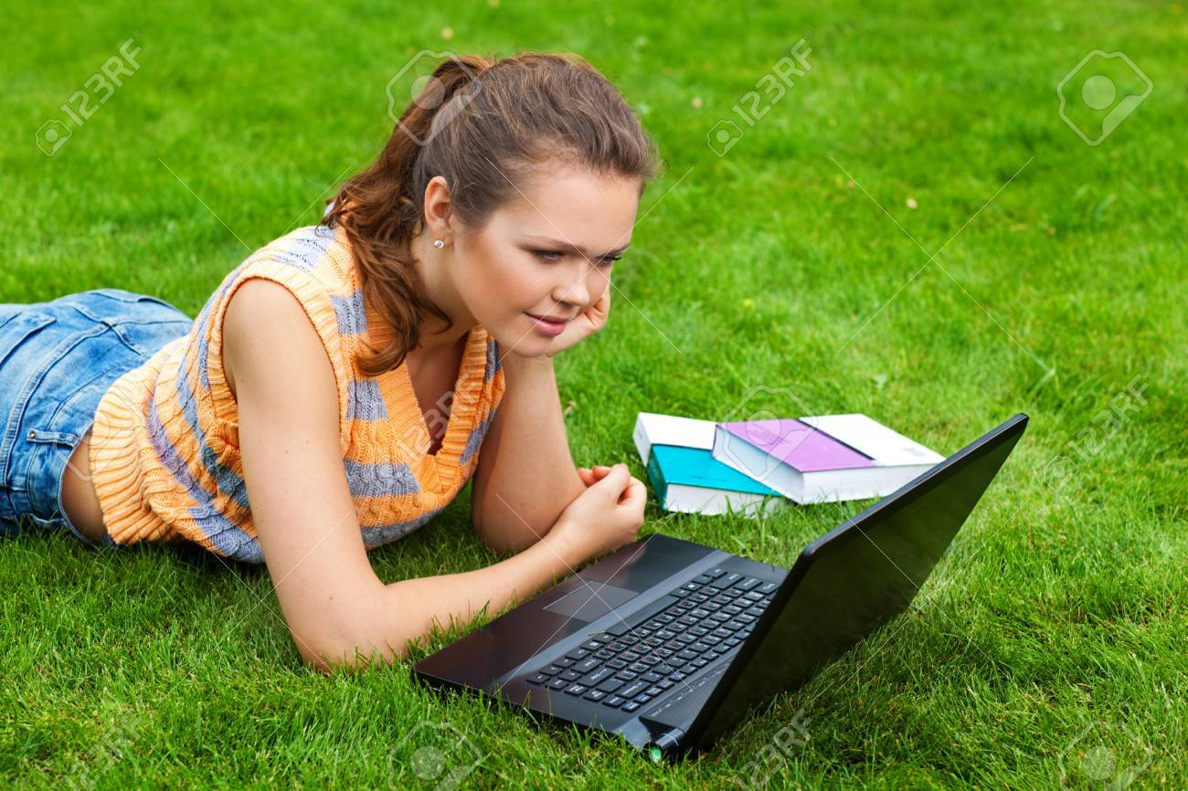 pretty young adult with laptop lying on green grass Stock Photo - 7586178