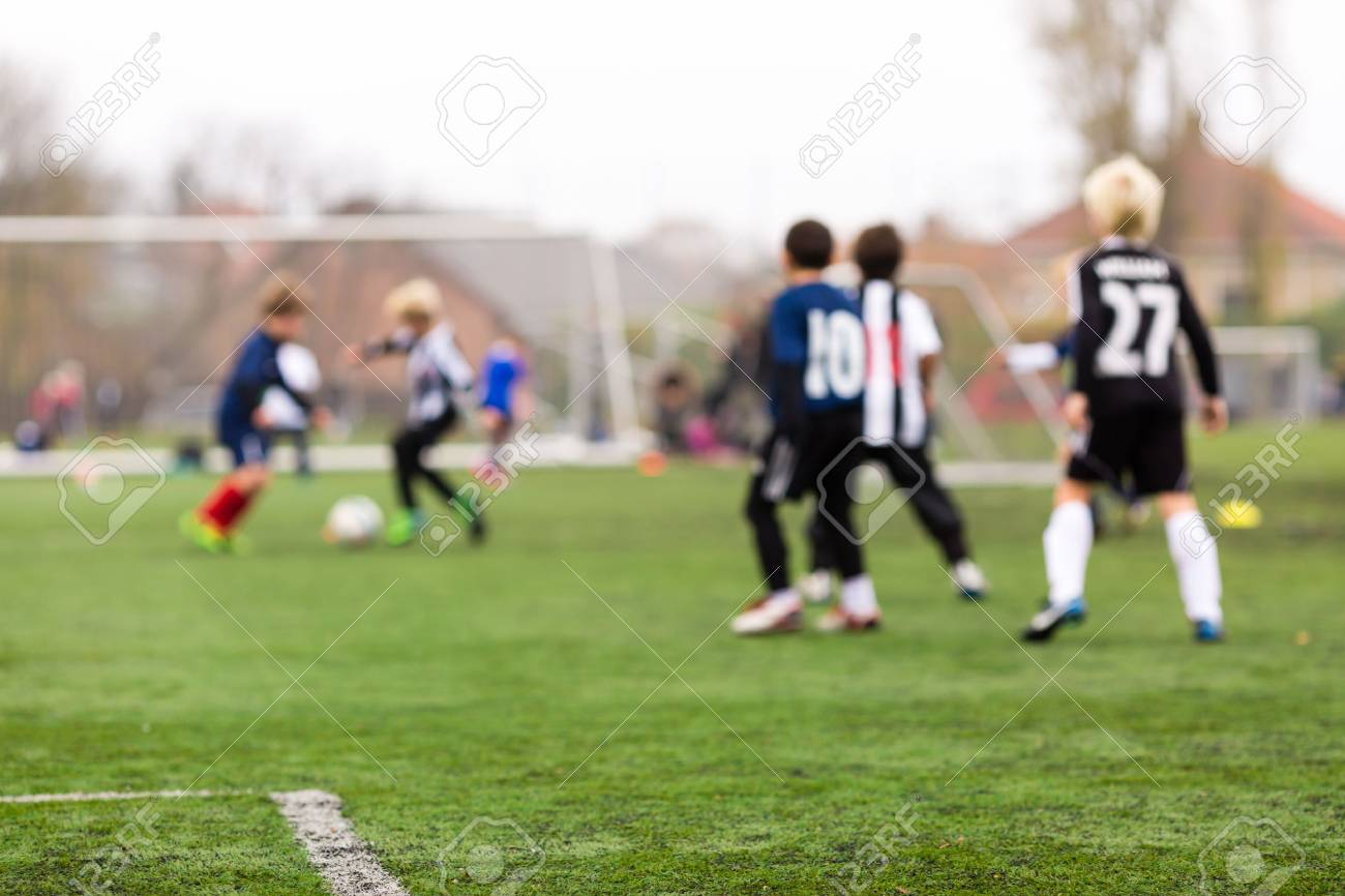 Young caucasian boys during a kids soccer training session on green turf. - 34008405