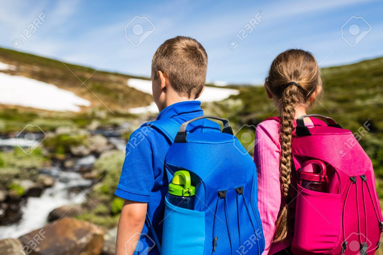 Two Kids On A Hike Wearing Their Backpacks And Exploring Nature