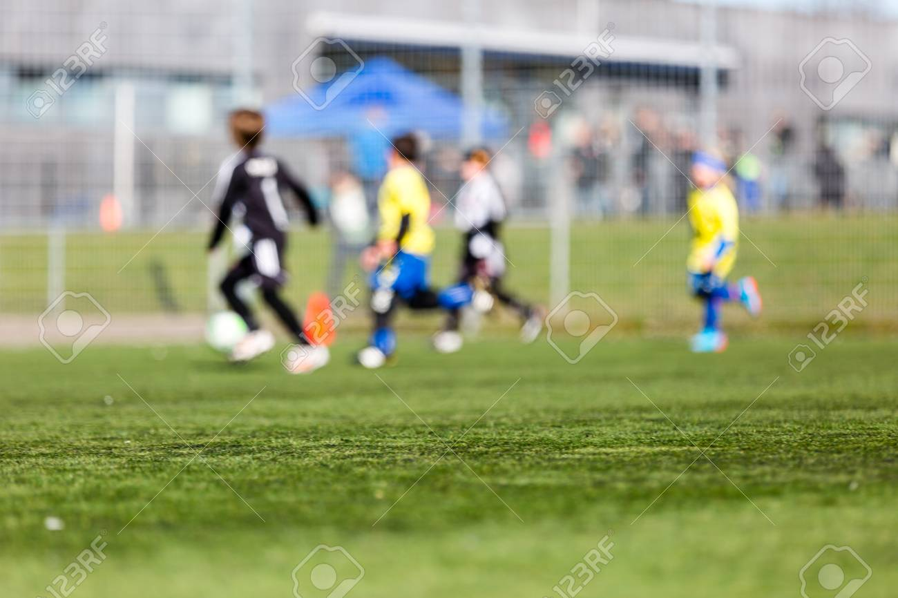 Blur of young kids playing a youth soccer match outdoors on an
