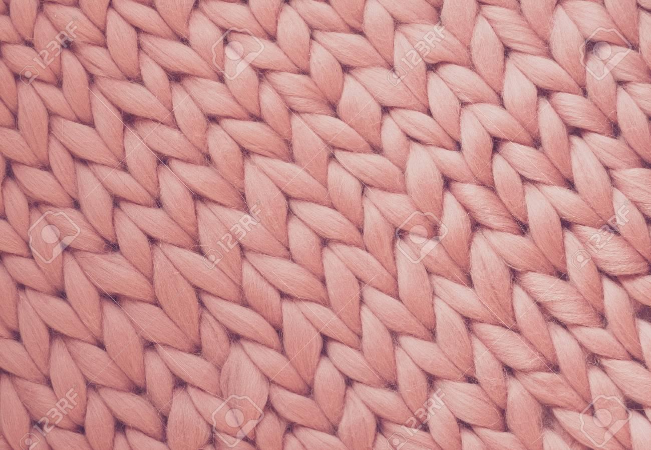 Texture of pink big knit blanket. Large knitting. Plaid merino wool. Top view - 104725629