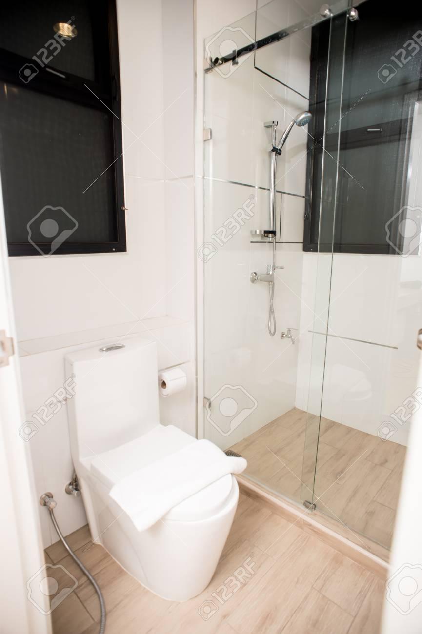 Sanitarios en el pequeño cuarto de baño con suelo de madera