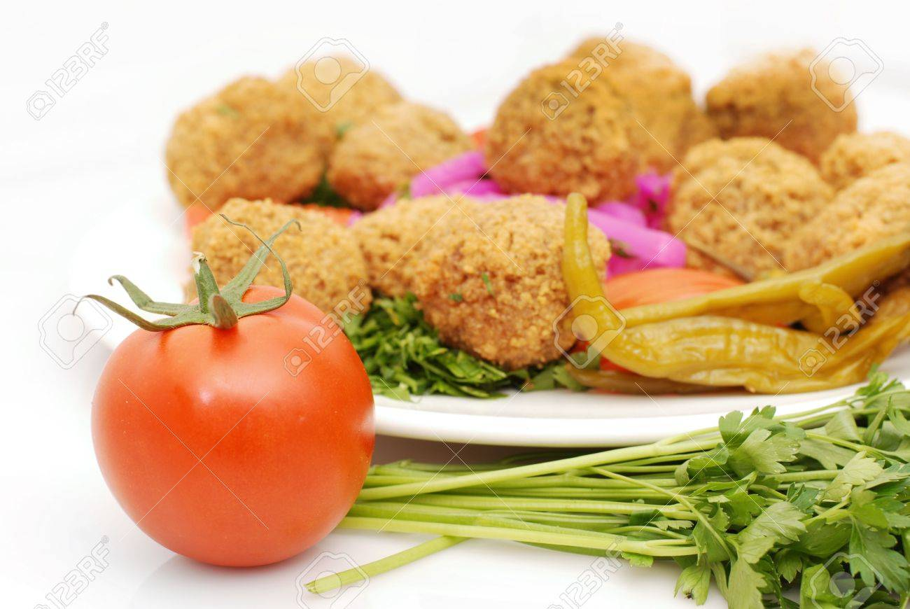falafel in pita bread dressed on a gold lined plate with tomatoes and lettuce with a garnish Stock Photo - 5429700