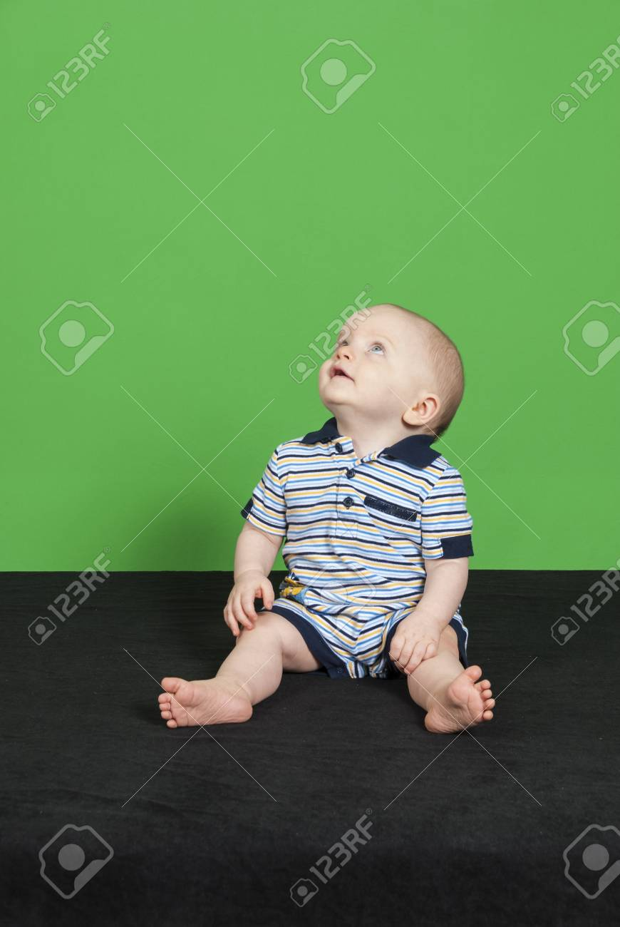 10 Month Old Happy Baby Boy on a Green Background Playing Looking Up Stock  Photo -