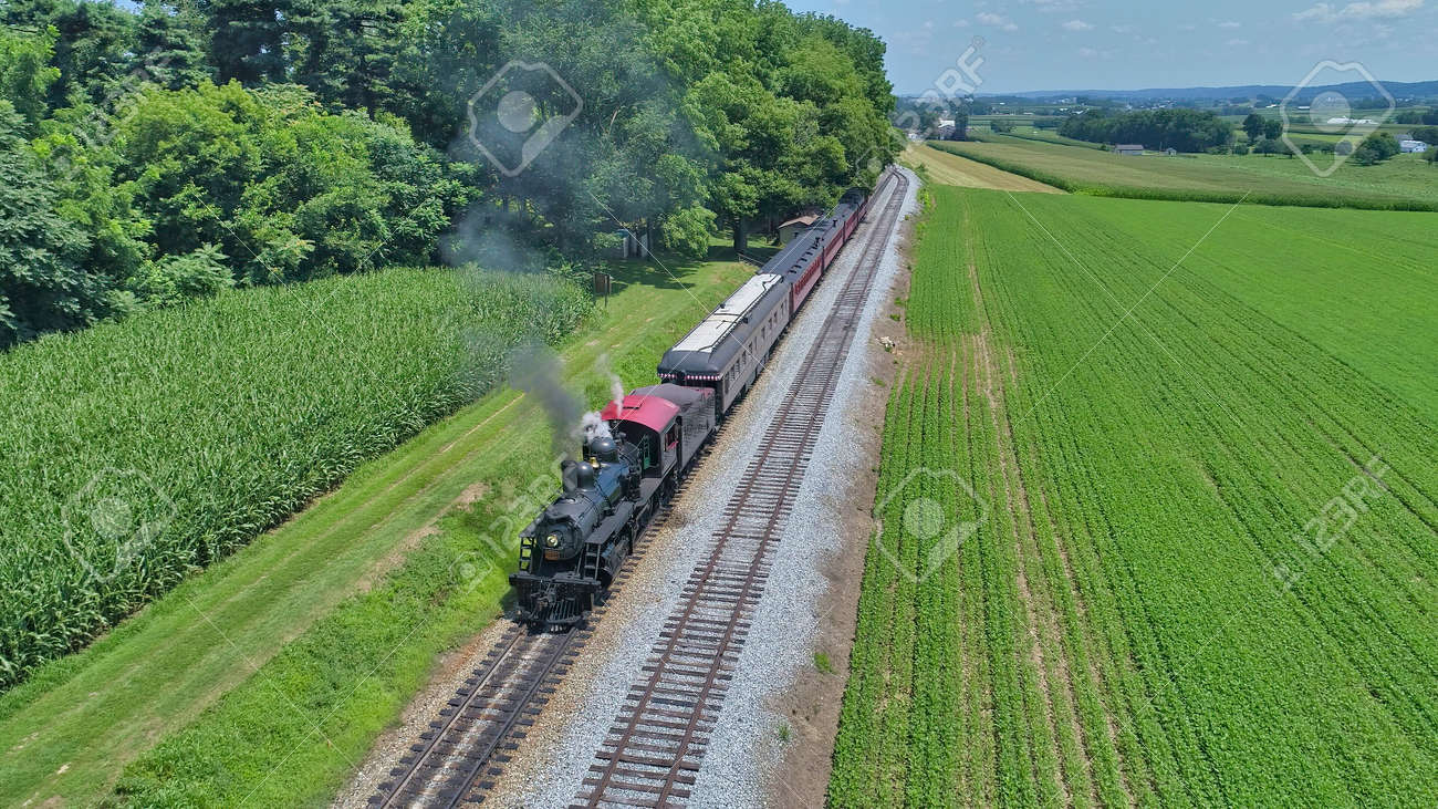 Aerial View of a Restored Antique Steam Engine and Passenger Cars Steaming Up at a Small Rail Road Station on a Summer Day - 162633880
