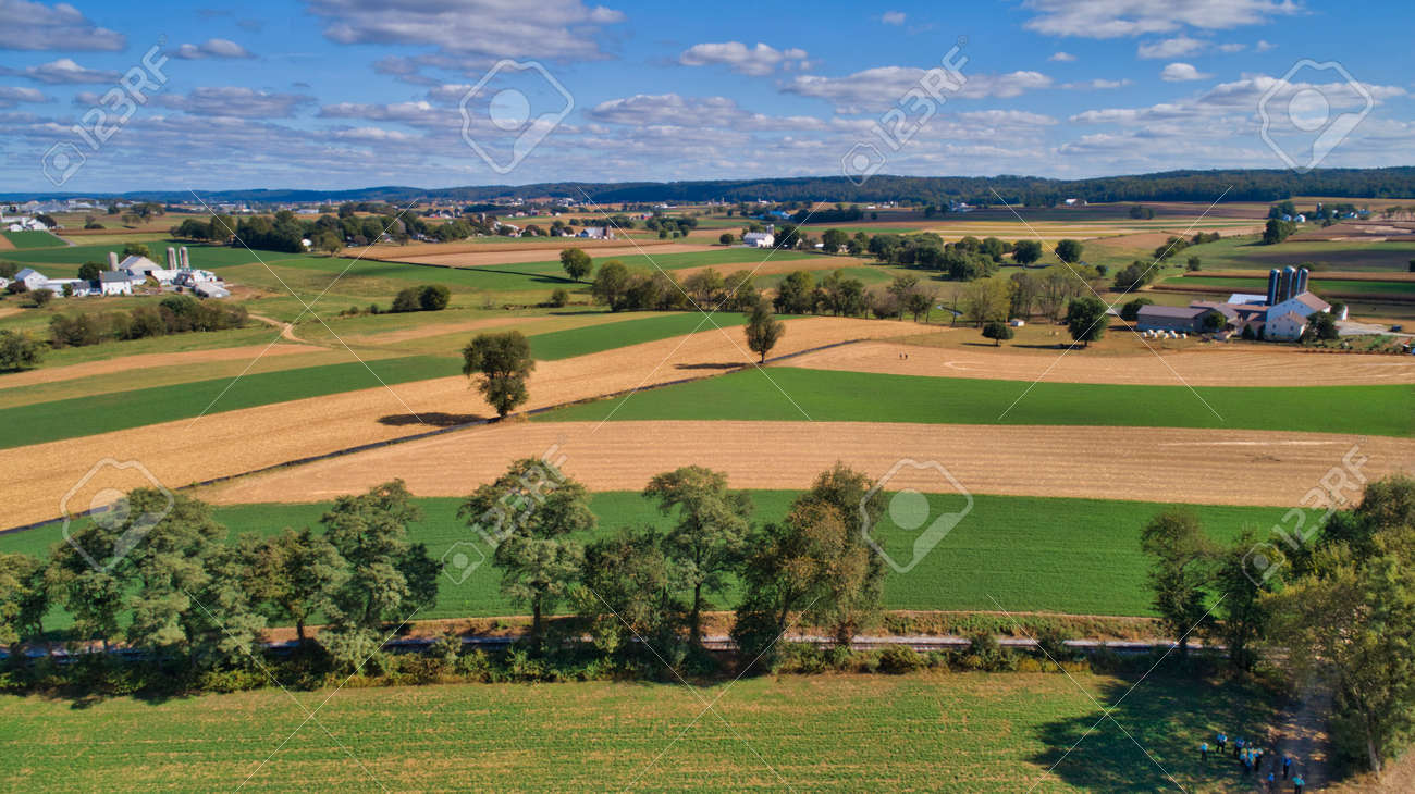 Aerial View of Multiple Farms and Train Tracks going Thru Them on a Beautiful Summer Day - 162633882