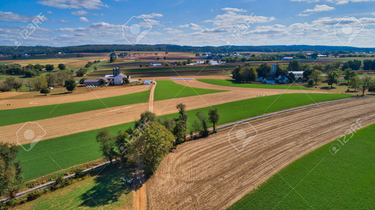 Aerial View of Multiple Farms and Train Tracks going Thru Them on a Beautiful Summer Day - 162633890