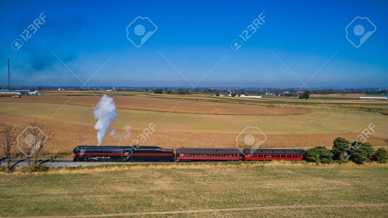 Aerial View of a Restored Antique Steam Locomotive Pulling Passenger Cars on a Sunny Fall Day - 162633885