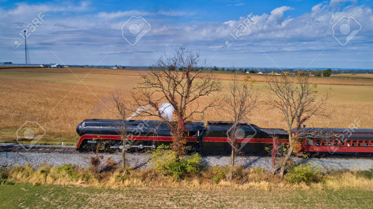 Aerial View of a Restored Antique Steam Locomotive Pulling Passenger Cars on a Sunny Fall Day - 162658453