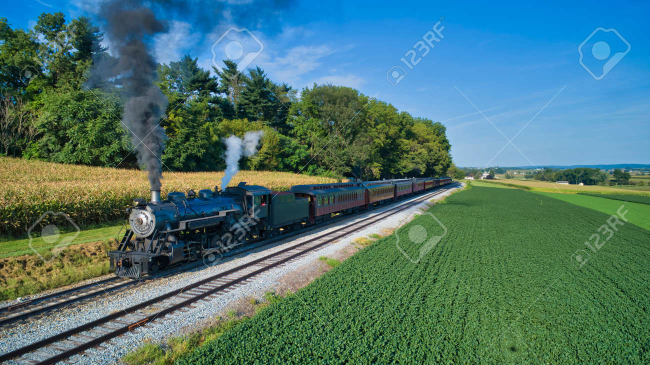 Aerial View of a Restored Antique Steam Engine and Passenger Cars Steaming Up at a Small Rail Road Station on a Summer Day - 162658454