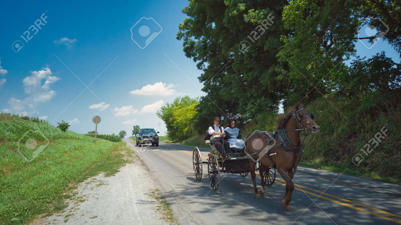 Ronks, Pennsylvania, July 2020 - An Amish Horse and Open Buggy With an Amish Couple in it on a Summer Day - 163318694