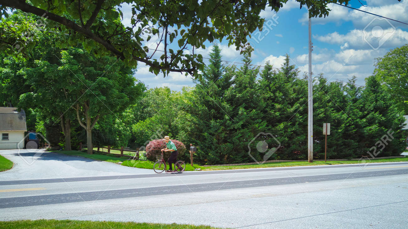 An Amish Boy Riding His Scooter on a Country Road on a Beautiful Summer Day - 162658461