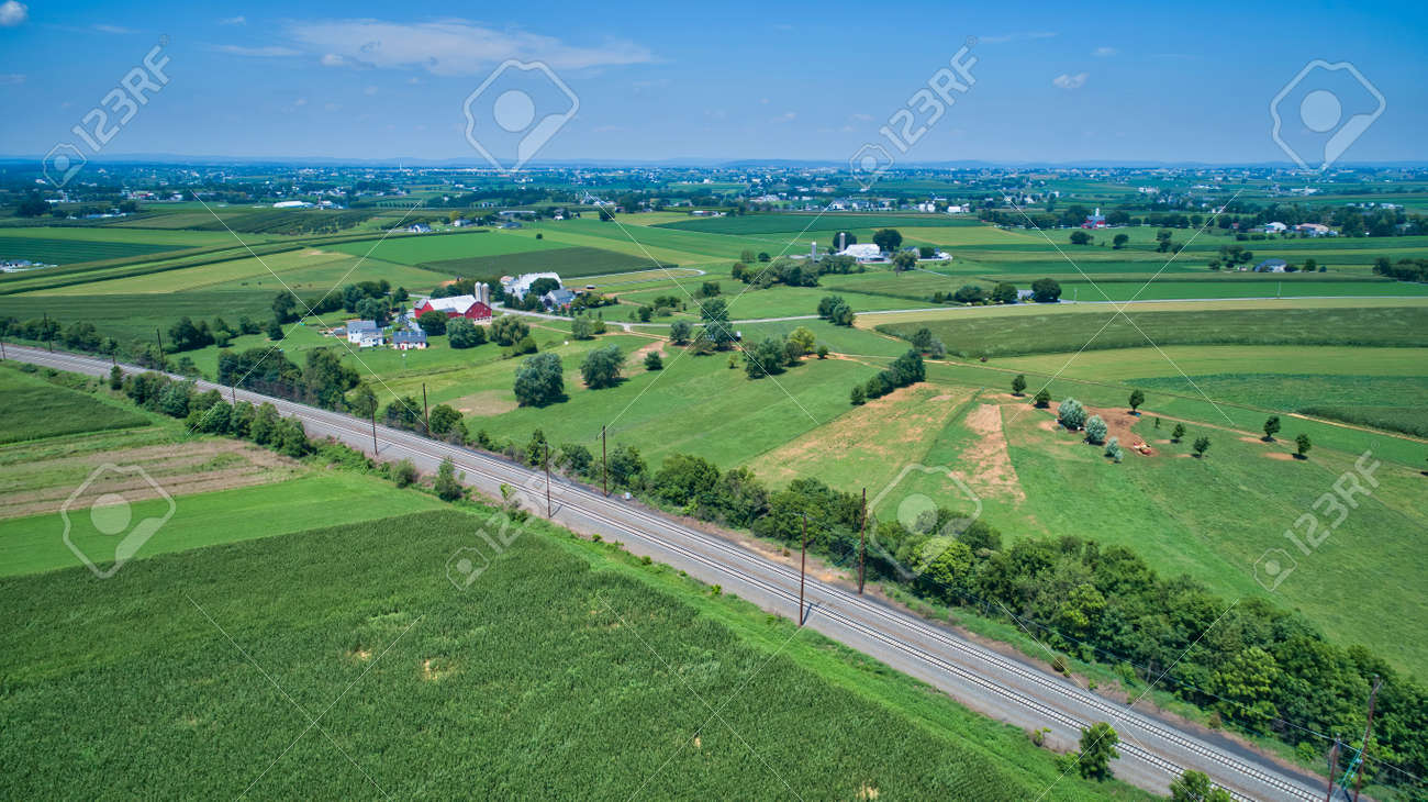 Aerial View of Multiple Farms and Train Tracks going Thru Them on a Beautiful Summer Day - 162658707