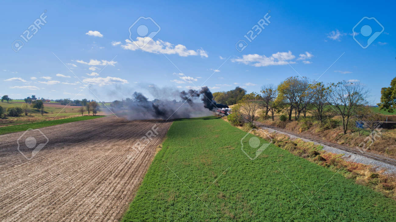 Aerial View of An Antique Restored Steam Locomotive Blowing Smoke and Steam Traveling Thru Farmlands and Countryside on a Sunny Summer Day - 165936885