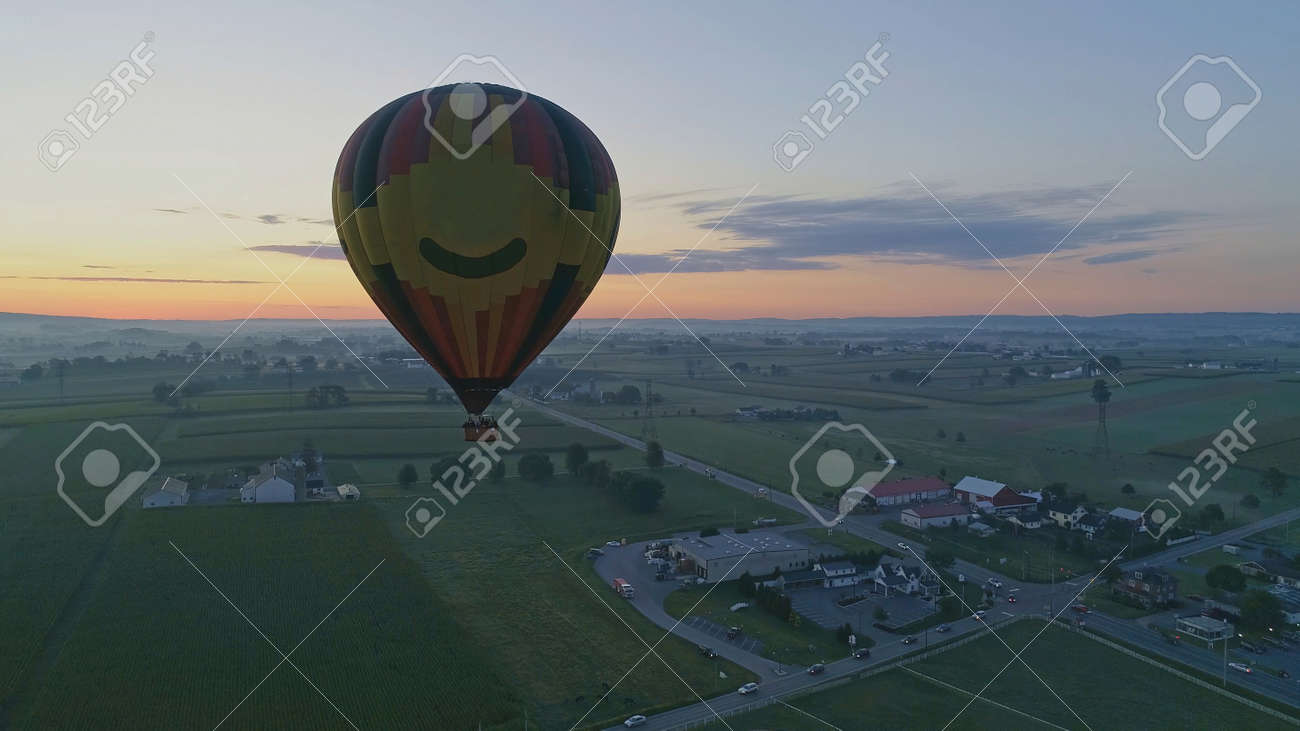 Hot Air Balloons Taking Off at Sunrise at a Hot Air Balloon Festival on a Misty Morning - 165159580