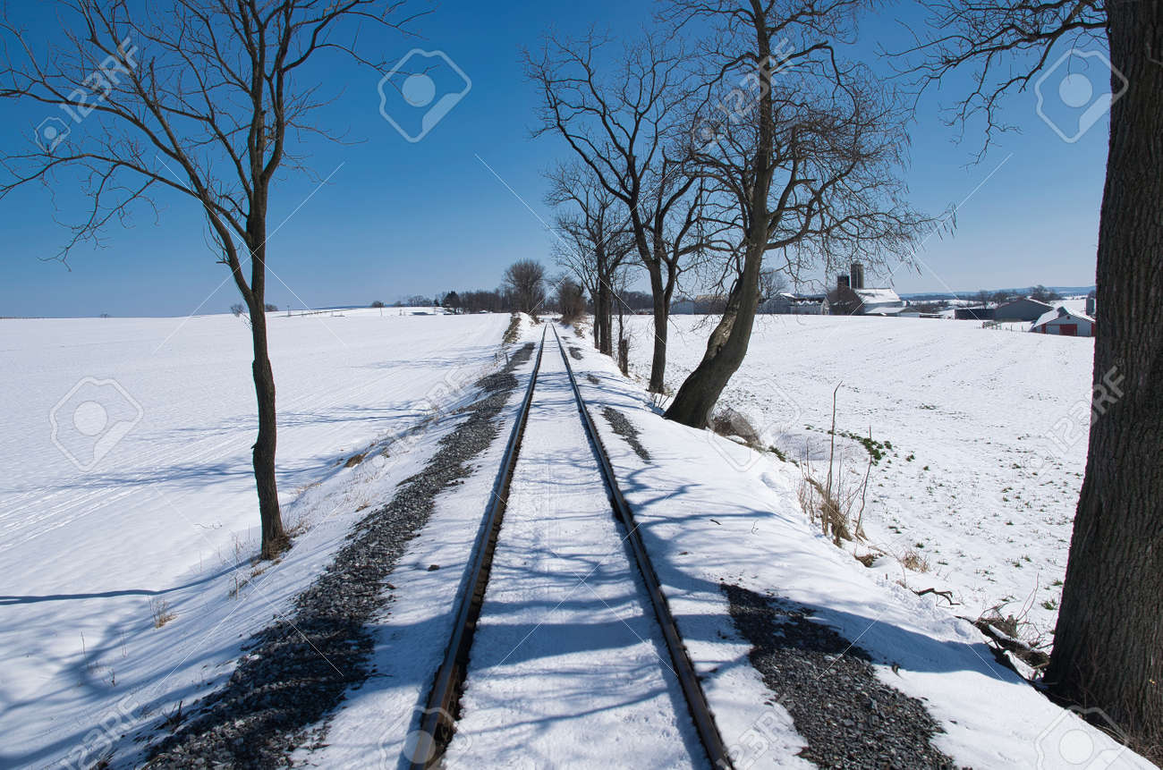 View of Rail Road Tracks Running Thru the Countryside Covered in Snow - 165159665