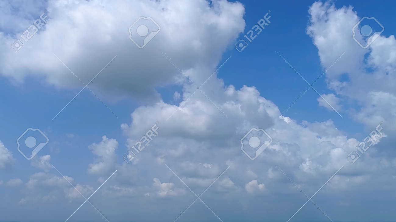 Blue Sky with White Fluffy Clouds as a Back Ground - 165159440