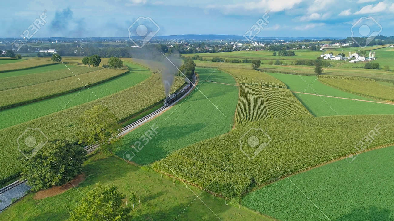 Aerial View of An Antique Restored Steam Locomotive Blowing Smoke and Steam Traveling Thru Farmlands and Countryside on a Sunny Summer Day - 165159328