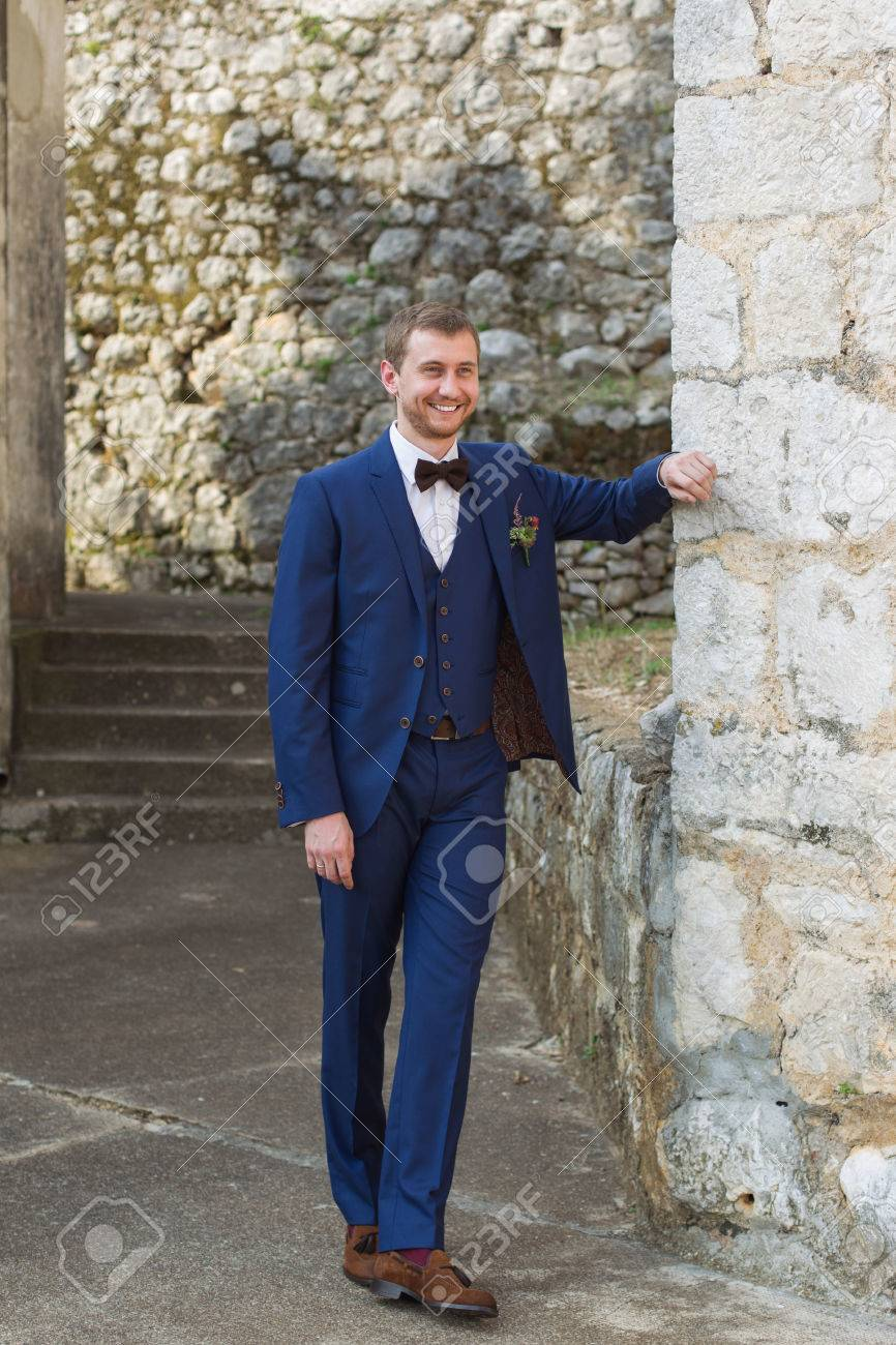 Handsome Groom In A Blue Suit Smiling Leaning On The Wall Stock ...