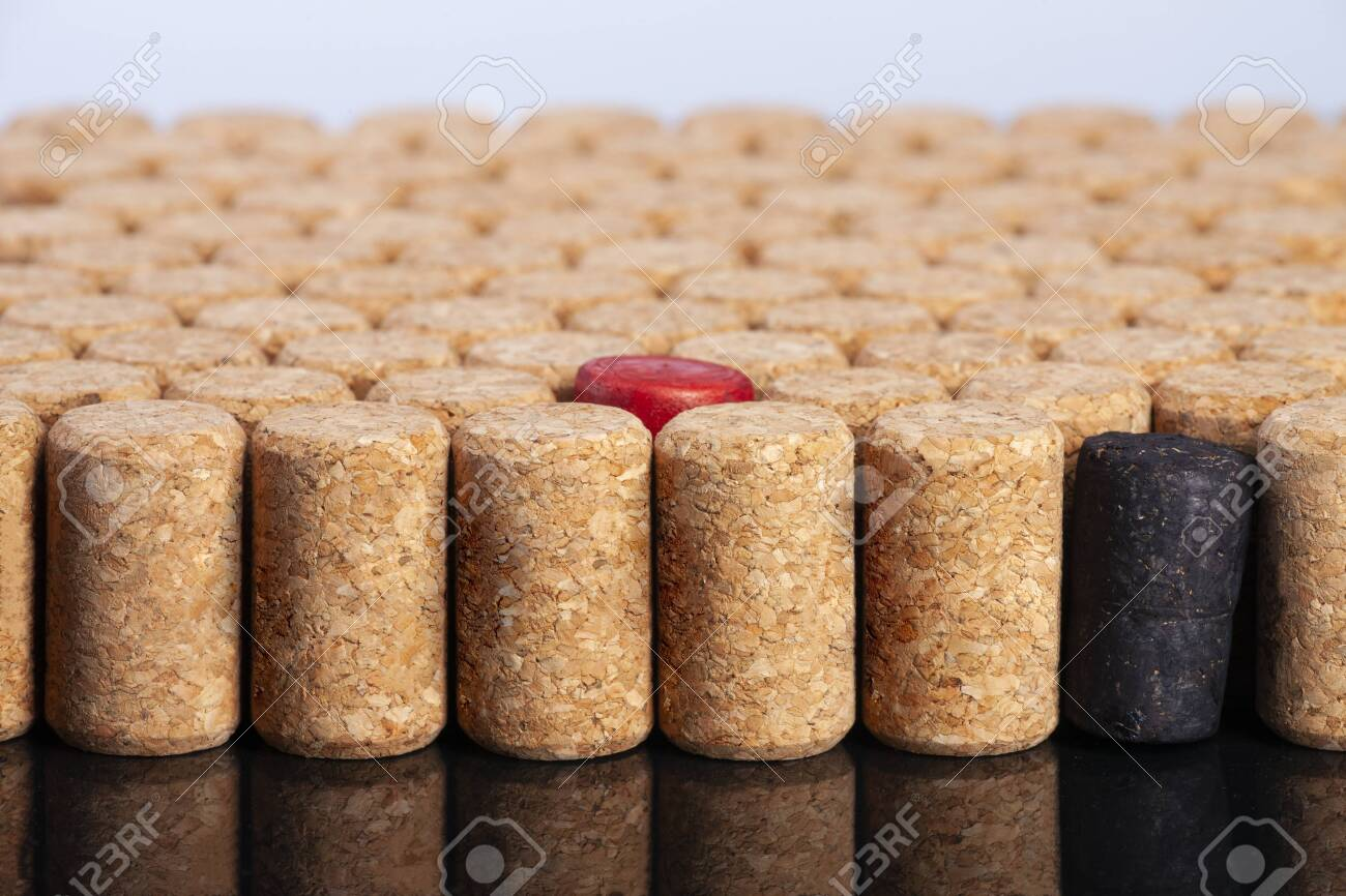 Many identical corks for wine. Red and black corks stand out. The concept of tolerance, the fight against racism and homobobia. Close-up. - 131911325