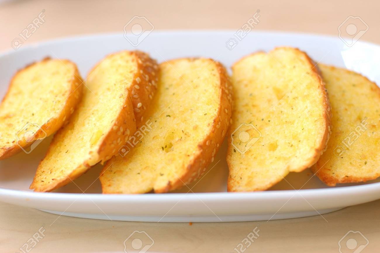 Garlic bread with herbs on white bread dish. Stock Photo - 11449219