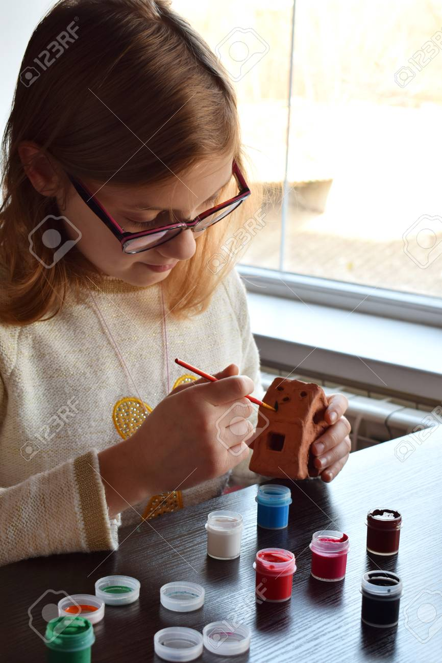 Girl making do it yourself toys paints a pottery clay toy with girl making do it yourself toys paints a pottery clay toy with gouache solutioingenieria Gallery