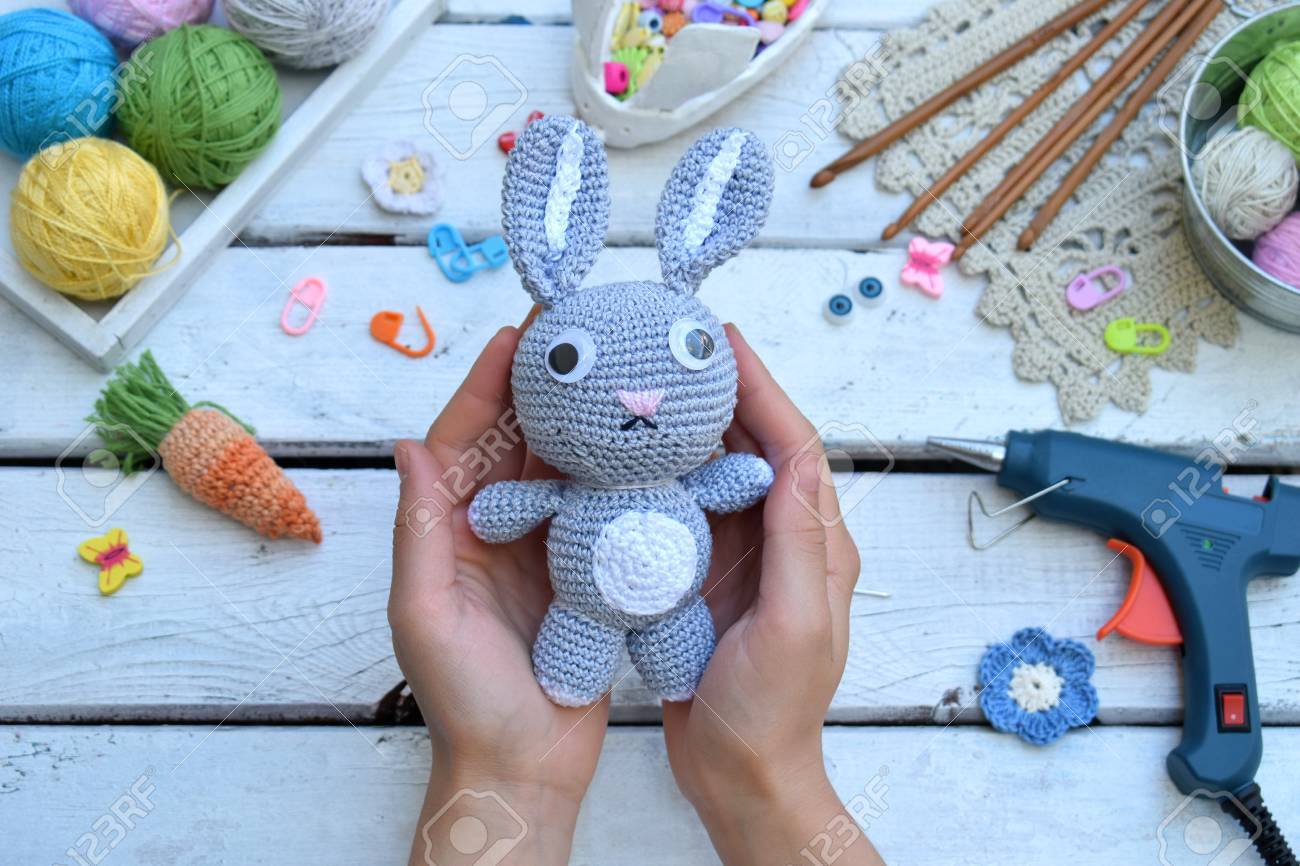 Making rabbit with carrot. Crochet bunny for child. On table threads, needles, hook, cotton yarn. Handmade crafts. DIY concept. Small business. Income from hobby - 106843055