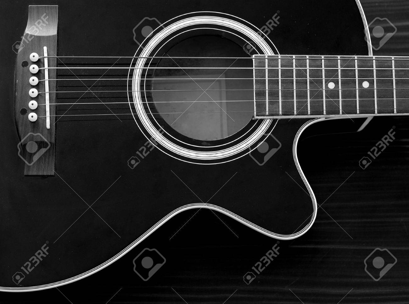Acoustic Guitar In Black And White On The Table Stock Photo
