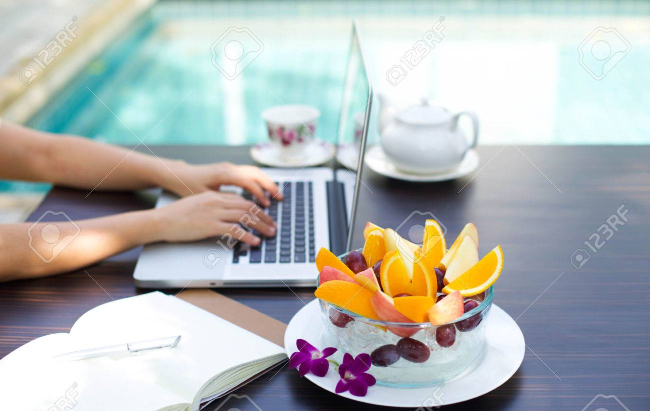 Business people working at home on laptop computer with blows of fresh fruit by swimming pool Stock Photo - 38967991