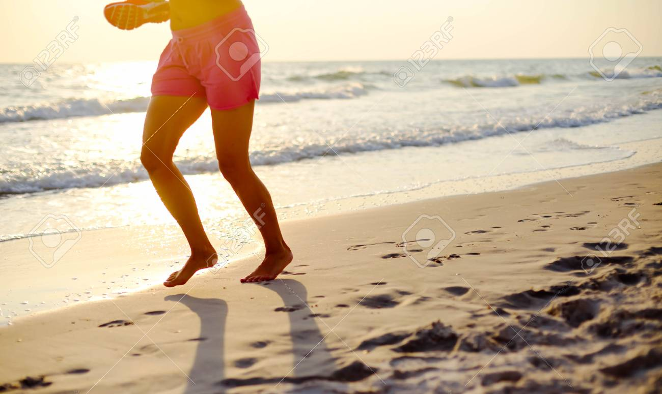Woman exercise running on the beach at sunset - 38968179