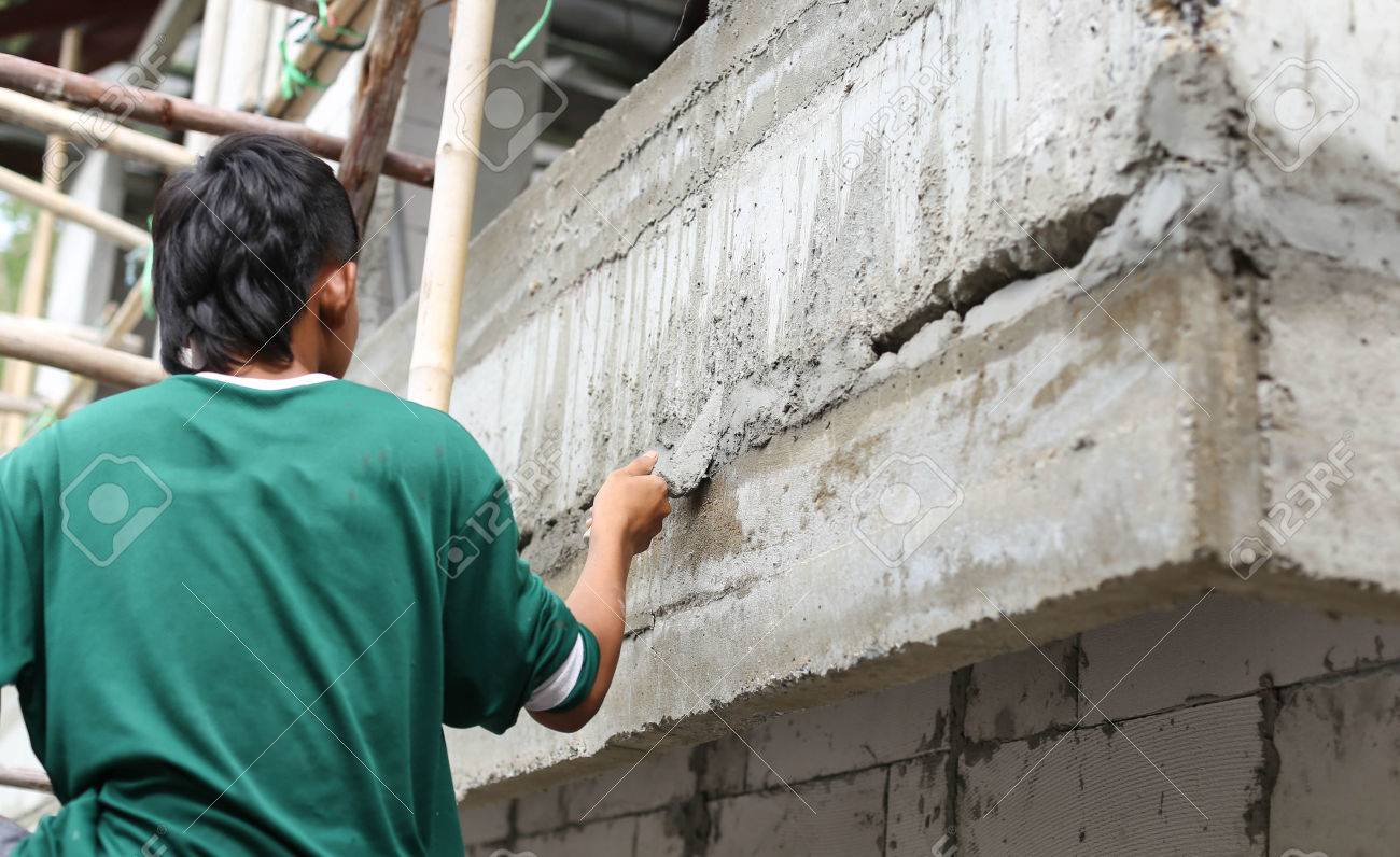 Asian boy hand using trowel with wet concrete wall in Thailand - 42911146
