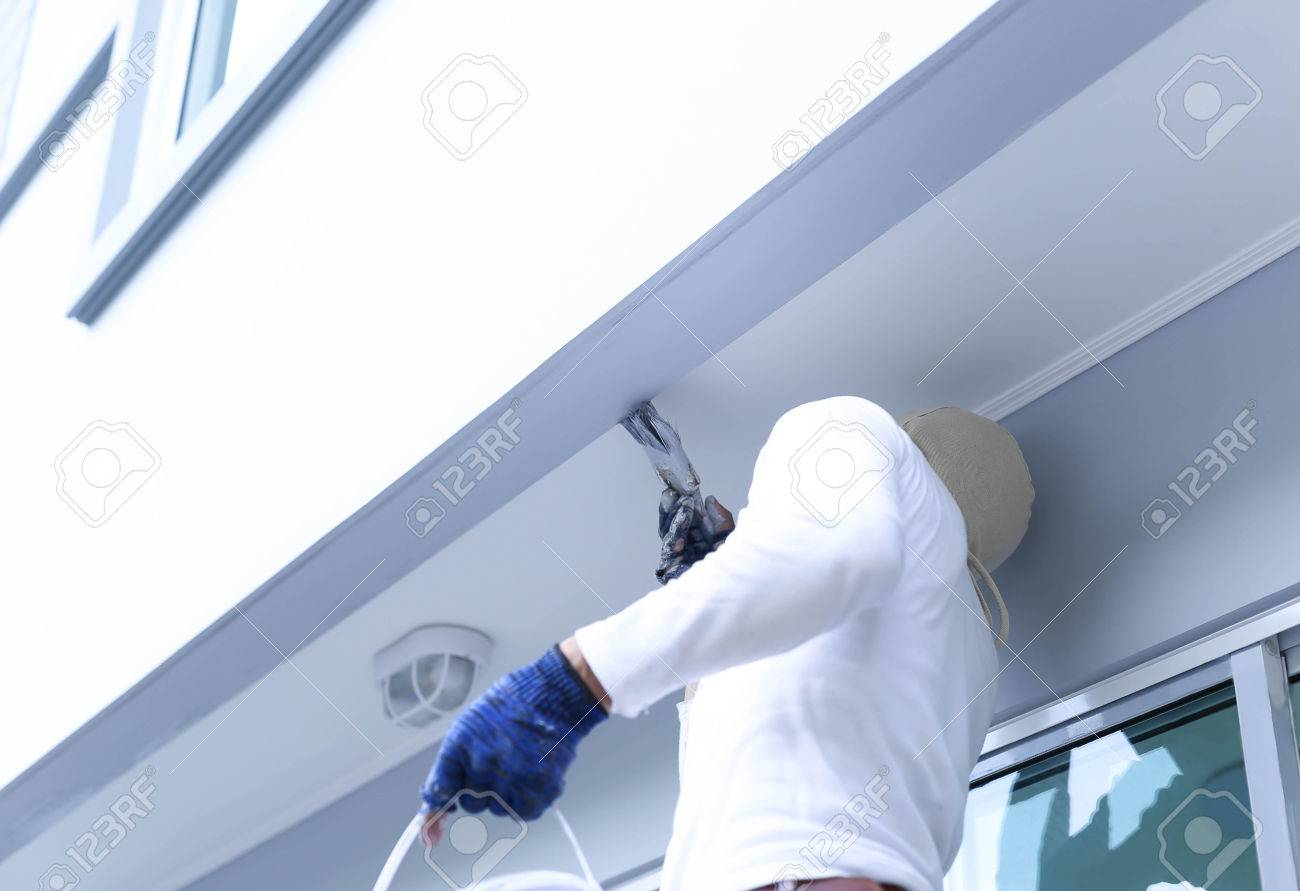Male in gloves holding pain brush painting building outdoors - 44684741