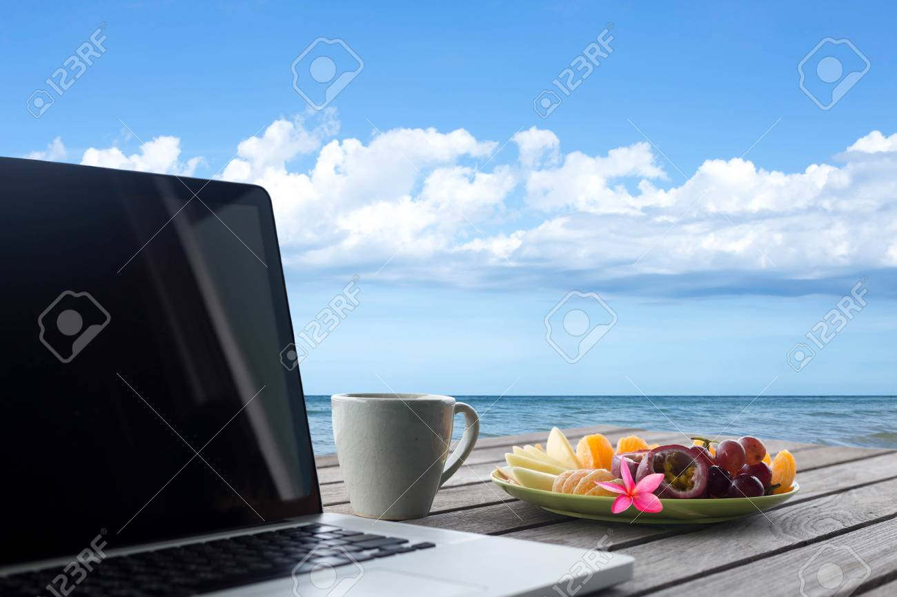 Selected focus mixes fruits and flower and laptop with coffee mug on wooden table top ocean view - 65477261