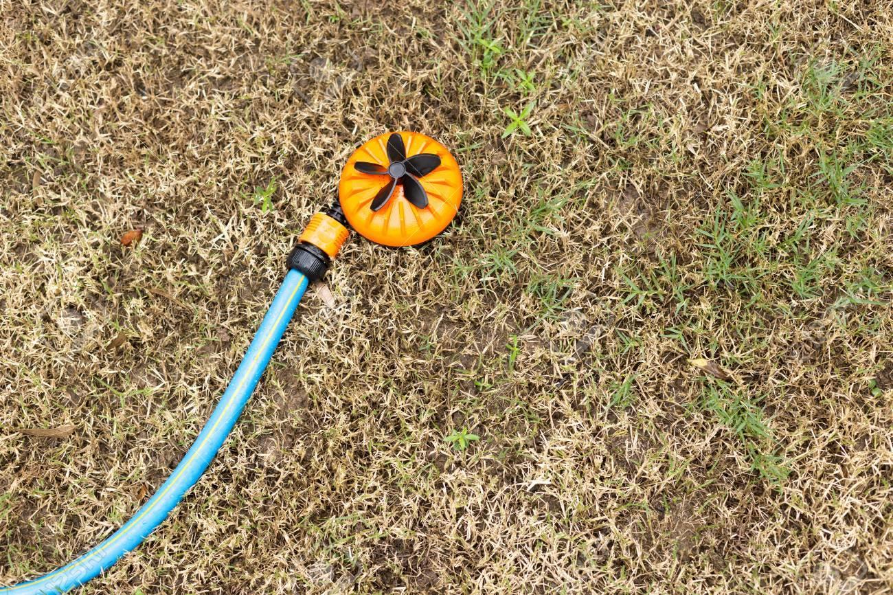 Orange Sprinkler In Dry Grass In The Garden Stock Photo, Picture And ...