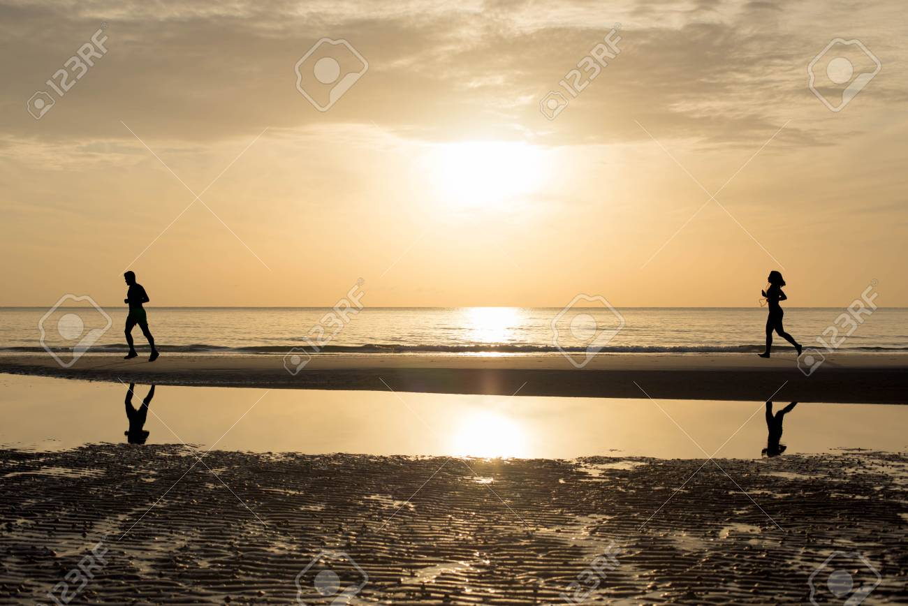 man and woman running together on the beach in sunset sunrise