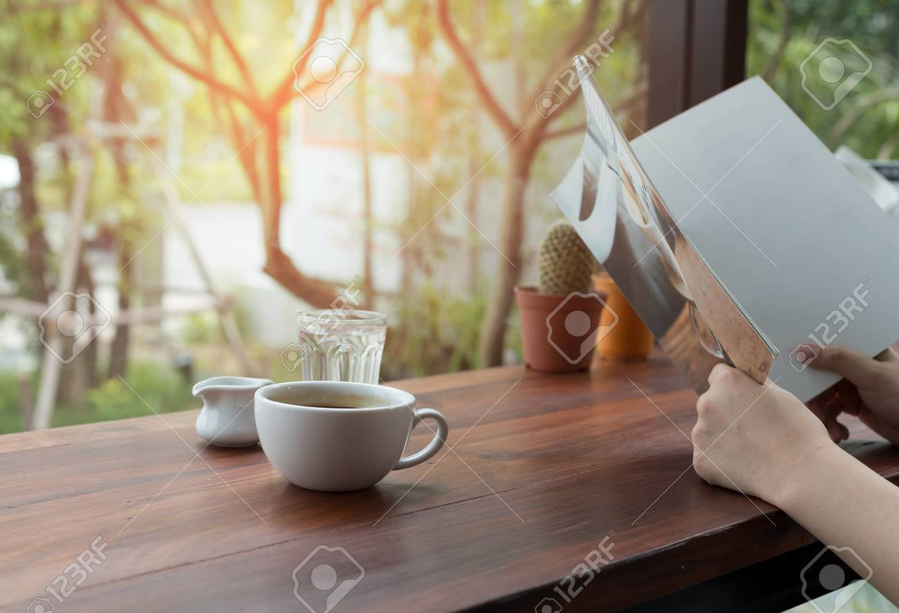 Asian people reading book and fresh cup of coffee on the table - 91199855