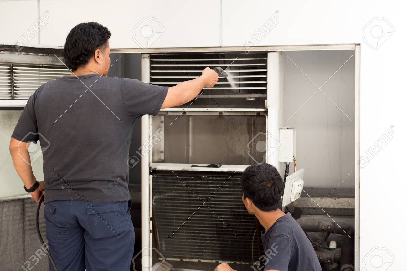 Unidentified man cleaning conditioner filter with high pressure