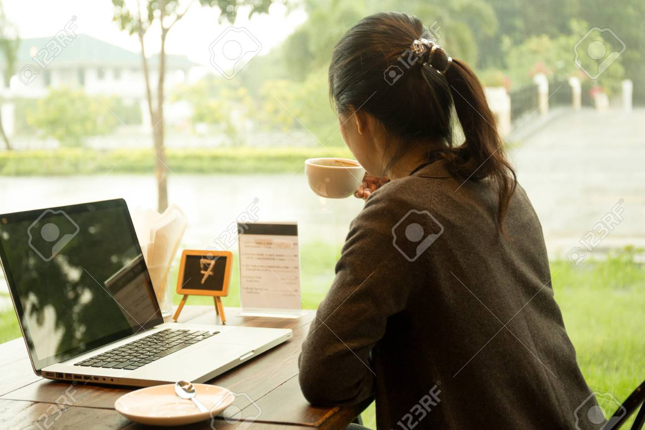 Asian woman with laptop having coffee watching the rain out of window - 84408560