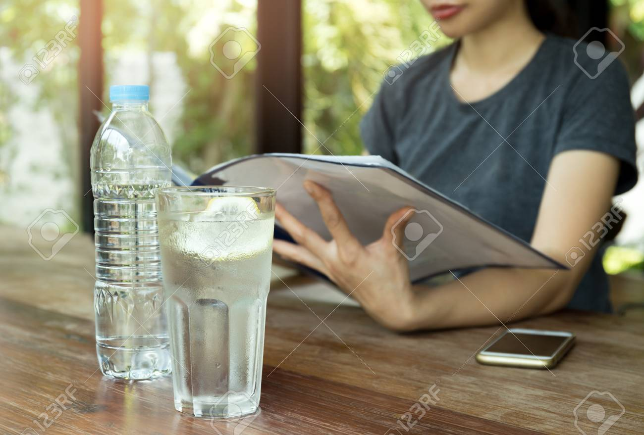 Fresh glass of water with slice of lemon and cell phone on with