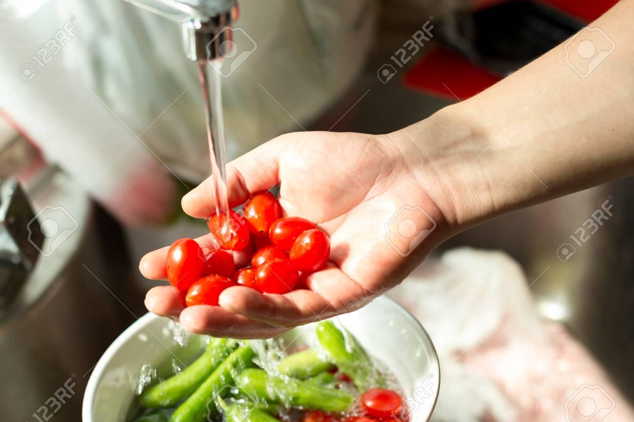 Hands washing fresh cherry tomatoes in running water in kitchen sink - 85888897