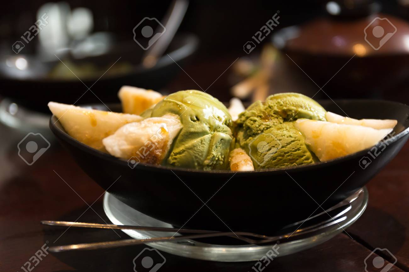 Shot in low light high iso Matcha ice cream scoop in bowl on wooden table Stock & Shot In Low Light High Iso Matcha Ice Cream Scoop In Bowl On.. Stock ...